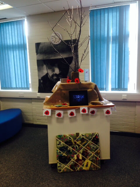 Library display with poppies, bare branches, b&w photo for Remembrance Day.